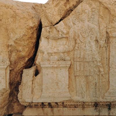Dieu en habit militaire, sculpté sur l'une des poutres placées à l'entrée du temple de Bêl, offre des fruits (grenades, pommes de pin). Palmyre