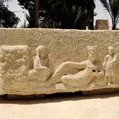 Bas relief : représentation majestueuse, presque grandeur nature, le père porte la coiffure des prêtres, ceinte de feuillage, son fils en toge se tient debout derrière lui, sa femme assise à l'extrémité. Musée archéologique de Palmyre Syrie