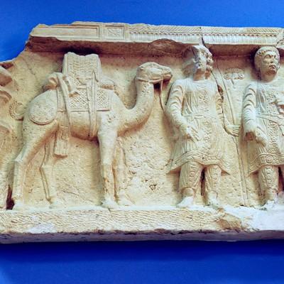 Ce chameau, tout harnaché avec sa haute selle posée sur une housse brodée et recouverte d'une peau de mouton, est prêt au départ. Son conducteur est armé d'une lance et le chef de la caravane (à droite) tient une épée, tandis qu'un bouclier pend à l'arçon de la selle. La caravane devait être défendue contre les éventuels pillards du désert.