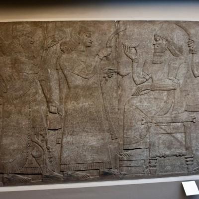 Assurnazirpal II, assis sur son trône, est vêtu du classique habit de cérémonie aux lourds drapés et richement orné, surtout sur la poitrine ; il est coiffé de la tiare tronconique à pointe qui symbolise la royauté ; un long pan de tissus associé à la tiare retombe sur son dos.