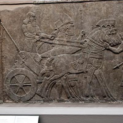 Ashurnasirpal est descendu de son char pour examiner un cortège de courtisans et de prisonniers de guerre. Un soldat assyrien, baise les pieds du roi, c'est probablement celui qui s'est le plus distingué dans les combats. la procession se poursuit sur le panneau à droite.