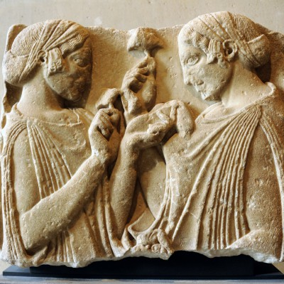 Cette stèle funéraire plutôt que votive met en présence deux, femme vêtues d'un péplos de laine coiffées d'un cécryphale dont l'extrémité retombe devant l'oreille. Elles tiennent des fleurs de pavot, ou de grenade, et peut-être un sac de graines.