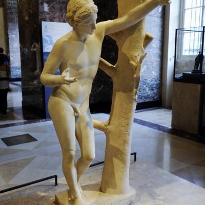 """350-340 avant J.-C. L'Apollon Sauroctone, c'est-à-dire """"tueur de lézard"""" est ici représenté sous la forme d'un adolescent prêt à attraper le lézard qui grimpe sur un arbre."""