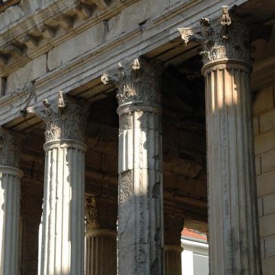 """LE TEMPLE DU CULTE IMPÉRIAL Le Temple d'Auguste et de Livie s'élève encore presque intact au centre de la ville au même titre que la """"maison Carrée"""" à Nîmes. Ce temple de style italique, entouré de colonnes sur trois côtés, se dressait sur un haut podium. Il présente deux factures différentes, visibles au travers des chapiteaux corinthiens, des modillons, et des caissons qui supportent la corniche, qui attestent deux périodes de construction. Des critères stylistiques permettent de situer la première dans les années 20-10 av. J.-C. Le temple est probablement dès lors dédié au culte impérial."""