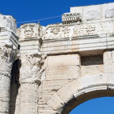 Le jardin archéologique de Cybèle Près de la place du Pilori deux grandes arcades perpendiculaires, construites en gros blocs de calcaire tendre. L'une d'elle offre une frise décorée de motifs végétaux encadrée de deux masques de personnages mythologiques. Mots clés arcades, portique, frises décorées, masques, personnages, mythologiques.  construites en gros blocs de calcaire tendre. L'une d'elle offre une frise décorée de motifs végétaux encadrée de deux masques de personnages mythologiques.